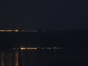 Lights in the distance across the Sea are soft on the hillside.